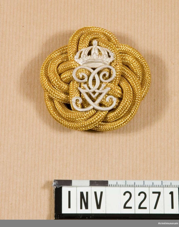 Samhörande nr är 2249-2281, 2806, 3281-3299, 3400-3409 (2270-2271). Valknut m namnchiffer m/1908, G V A. Guldsnöre flätat till en platt knut varpå Gustav V Adolfs namnchiffer m/1908 i silver vilar.