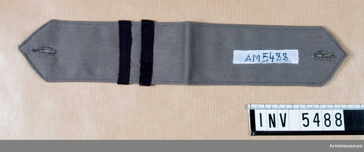 Av grått bomullstyg i kypert. Knapphål i båda ändarna. Två mörkblå gradbeteckningsband av kläde (motsvarar korprals tjänsteställning), 5 mm breda. Placerade på tvären, det första 25 mm från vikningen.Gåva av E Lindberg, f Bokelund, Halmstad. Se AM 3635.