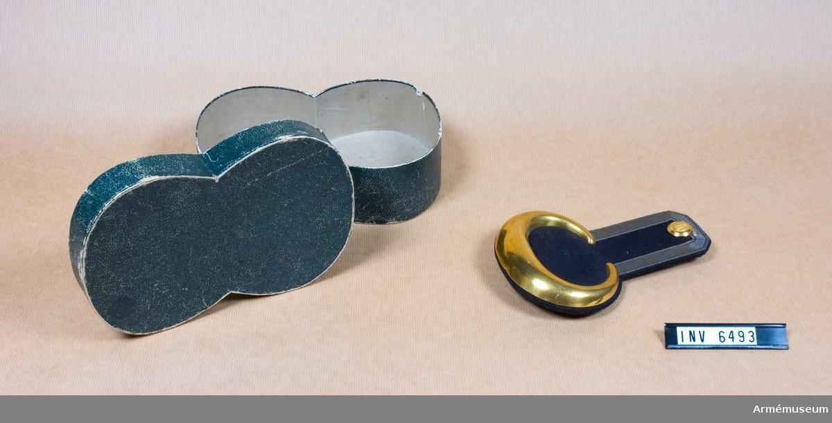 """Mörkblå klädesmatta/foder, guldgalon runt epåletthalsen och en massiv, förgylld metallplåt runt nedre delen. På den övre delen en större knapp av reg:s modell. Haken märkt """"CA&AD EK""""."""