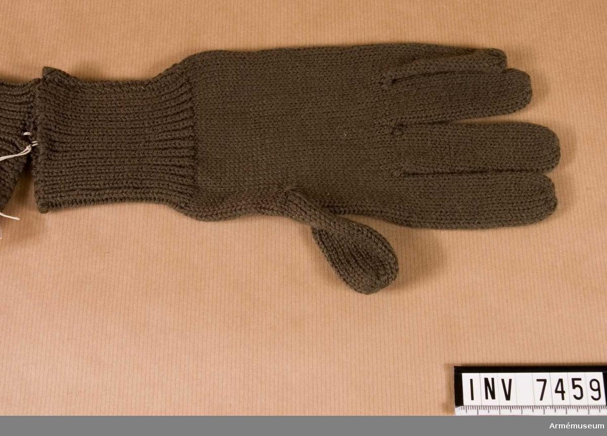 Färg grågrön Q P. Stickad av gröngrått yllegarn och har fem fingrar.   Samhörande par är AM.7458-59