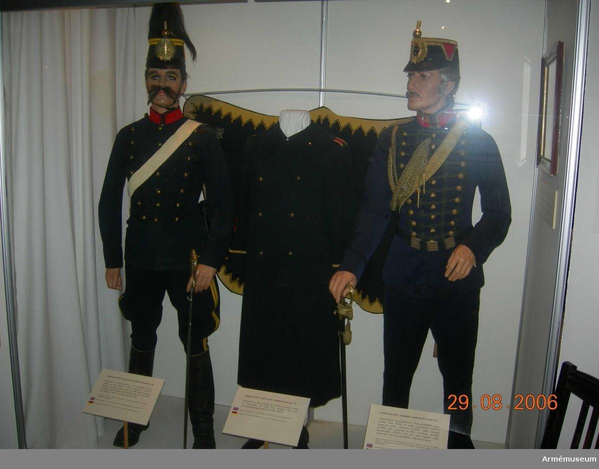 Mörkblå, hög mössa med svart lackskärm framtill och baktill. Kulle av svart lackskinn. På sidorna s k chevron klädd med rött kläde. Guldgalon löper runt kullens övre sidor och den undre kantar chevronen. Mitt fram mössmärke m/1880 (käppiplåt) för officer vid artilleriet. Färg mörkblå och röd M G.  Käppi infördes år 1880. Till den användes samma märke såväl till daglig dräkt som till parad. Vid parad tillkom pompong och vid stor parad plym. För officer förgylld med blåemaljerad sköld och rött foder i kronan, för underofficer helt förgylld. För manskap blankpolerad mässing.