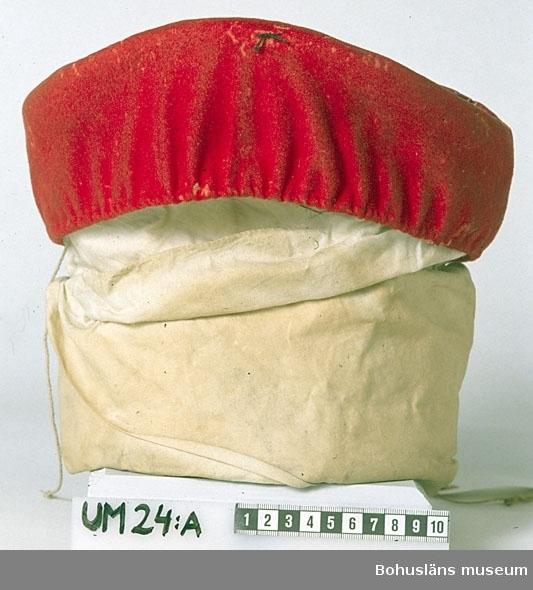 Huvudbonaden består av tre delar. En timglasformad stomme sydd av halmflätor, en dubbelvikt vit linneduk virad kring stommen med vikningen längs stommens nederkant och en röd mössa av ylle (kläde), broderat med silke i svart och mycket ljust beige (gult som bleknat?). Mössan är gjord av ett cirkelformat stycke med en påsydd ca 8 cm bred  kant runtom. Över sömmen på rätsidan är en flätsöm sydd. På mössans  runda överdel finns ett stiliserat mönster, med en cirkelrund mitt omgiven av mönsterfigurer med hjärtan, sytt i kedjesöm. Hjärtmönstren är placerade utefter linjer, sydda i efterstygn, som delar in ytan i  åtta sektorer. Längs mössans nederkant finns en kanal för en snodd av lingarn, att dra ihop mössan med. Den hänger ut genom ett hål med en metallöljett. Stommens form är uppböjd upptill mitt fram. Invändigt finns en trälist som håller ut formen fastsydd där. I huvuddukens vikning sitter ett  papper fastnäst. Siffror och text syns. På mössan finns en svart trådände fastsydd fram. Den hör troligen  till en gammal etikett. På tidigare katalogkort finns ett foto där etiketten syns.  Angående givaren N P Hamberg och de sk Hambergska samlingarna som han  skänkt museet se Knut Adrian Anderssons katalog I:141-143, D 2 A:1  i museets arkiv.  Linnekluten är mycket smutsig och har små mögelfläckar. Mössan är sliten. Den har små hål längs kanten och på höger sida, troligen gamla insektsangrepp.  Litteratur: Nylén, Anna-Maja, Folkdräkter, Stockholm 1949, sid.108-109. Folkdräkter ur Nordiska musees samlingar, Nordiska museets handlingar 77, Lund 1971, sid. 61.  Folkligt dräktskick i Västra Vingåker och Österåker Nordiska museets handlingar 27, Uppsala 1947, sid. 134-139.  Ur handskrivna katalogen 1957-1958: Kvinnodräkt från Vingåker. a) Mössa, röd m. broderier. Stomme av halm. b) Svart kappa m. silverspänne  (1600-1700-börj av 1800-talet) Malhål. c) Rött bältem. metallbroderier. Trasigt. d) Blusliv vitt m. i rött broderad hög krage.  Lappkatalog: 76