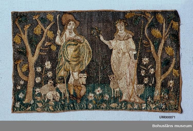 """Broderi på beige linne. Motivet är en herreman (herde?) och en kvinna (herdinna) med fem får, en hund samt en vilande ko. Kring figurerna finns träd och blommor. Mönstret är gjort av silke huvudsakligen i schattérsöm, mitten i vissa blommor broderade med knutar, några blad i läggsöm. Himlen i bakgrunden är sydd av metallöverdragen silketråd (troligen silver) i läggsöm. Färgerna i broderiet är (på baksidan) olika ljusblå nyanser, blågrönt, mörkgrönt, ljusgult, gröntonat gult, brunt, gulbrunt, beige, svart, två nyanser av mycket ljust rött (rosa). Silketråden vittrad i mannens hatt och skor; det har varit ett svartfärgat garn som på grund av mycket kemikalier vid färgning inte klarat sig.  Litet hål i överkanten. Brunt längs kanterna. Läggsömmen över några metalltrådar i ena sidan är borta. Mycket blekt.  Knut Adrian Anderssons katalog: 1:25.12 Broderi av silke och metalltråd på grå botten (=herde o herdinna) 32 x 20 cm. från 1700 talet. Skänkt av Göteborgs museum 3 april 1880. Är ett stycke av en bonad.  Ur handskrivna katalogen 1957-1958: """"Broderi m. silke o metalltråd 1870 Mått. 32 x 19 cm; broderi som ovan; herde och herdinna jämte djur; ngt defekt."""""""