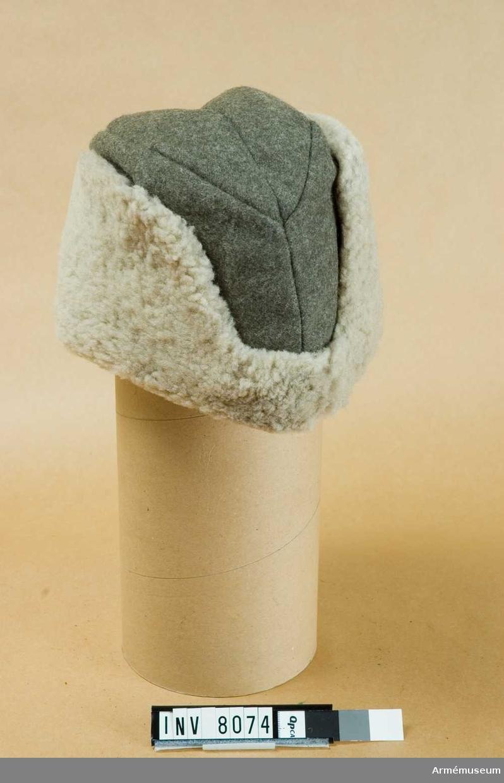 Storlek 57. Höjd 120 mm. Vidd 57 mm. Vikt 275 g. En mjuk fodrad och vadderad mössa (båtmössa) av gråbrungrönt kommisstyg, försedd med uppslag, klädda med grått pälsskinn, vilket kan vikas ned till skydd för öron och nacke. Därjämte är mössan försedd med särskilda öronskydd och tygskärm, som vid behov kan fällas fram. Nyskick 111.Se Uniformsbestämmelser för armén 1946.