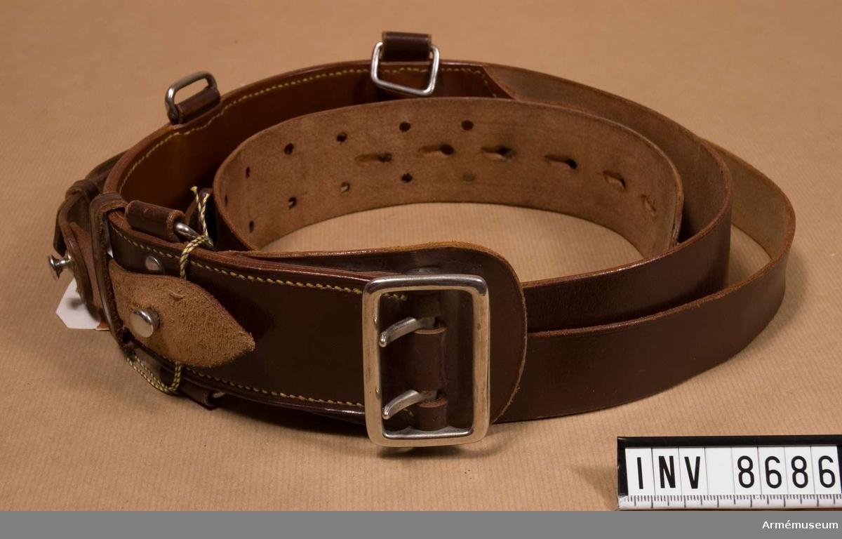 Av brunt läder med stålspänne och övriga beslag.