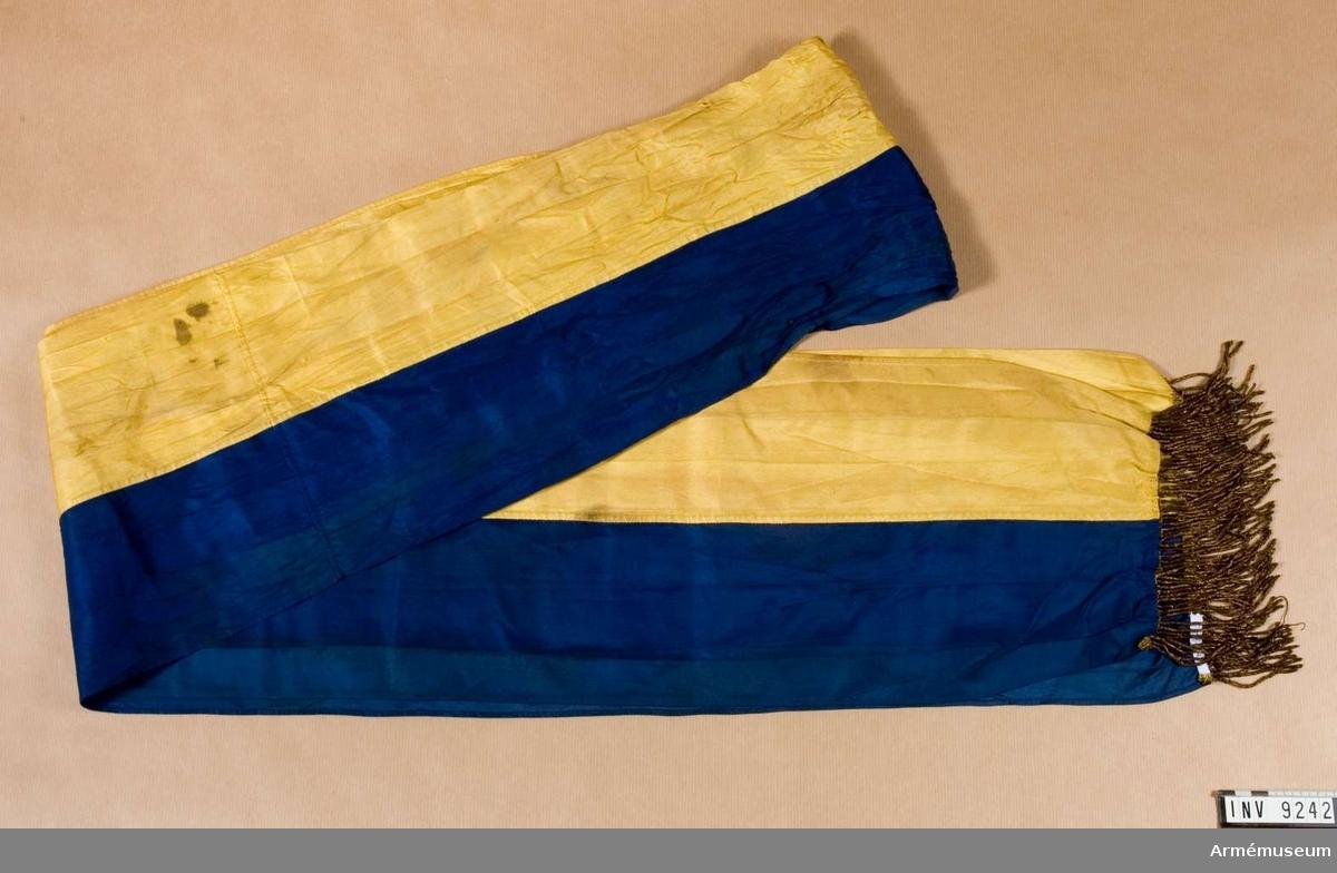 Sydd för hand av hälften mörkblått och hälften gult siden. Kortsidorna försedda med en enkel guldfrans.