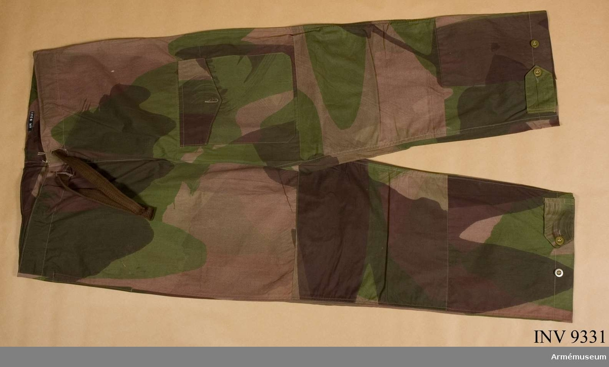 Maskering i grått, brunt och grönt är tryckt på tyget. Byxan har dragsko i midjan och extra lapp i baken. På vänster ben en stor ficka med lock, spetsigt med knapp och knapphål. Nedtill på benet en tamp för reglering av benvidden. På fastsydd tygetikett: Trousers, Windproof. Camouflaged. Size No 3.