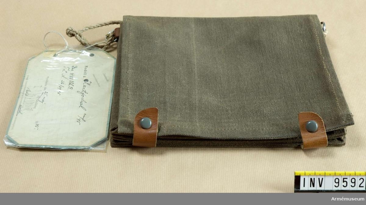 Av smärting med fack för karta och handlingar. Har bruna  läderremmar och rep över axeln. Fastställt 25 maj 1945.
