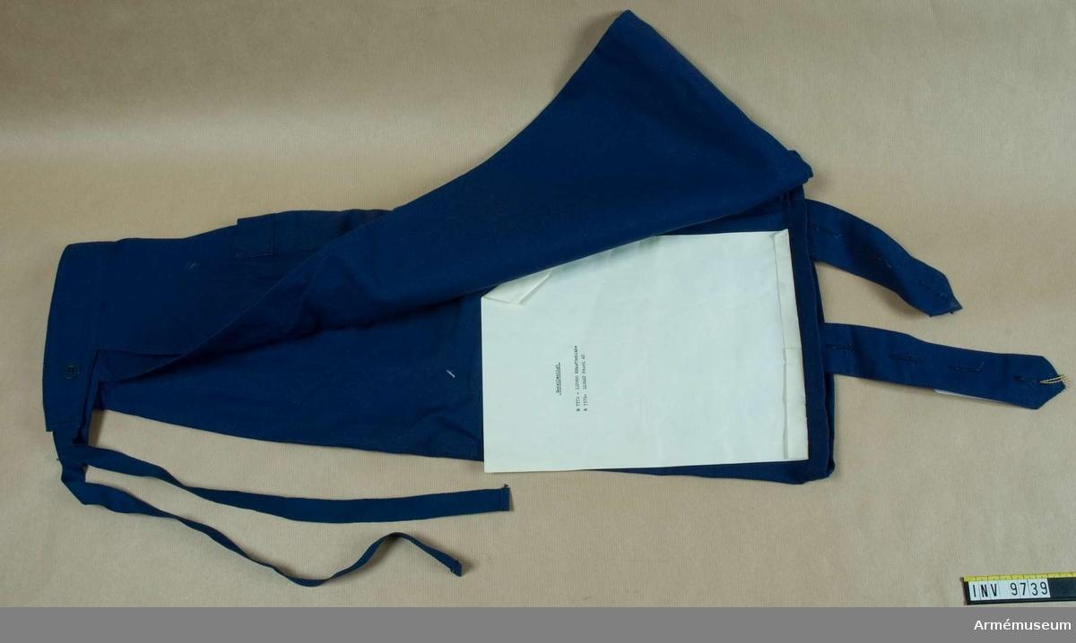 Mörkblått bomullstyg av twillstyp. Sytt med bröstlapp med hängslen. Ficka på höger sida.
