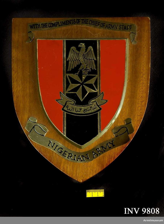 Gjord i form av en sköld brun trä varpå vilar en emaljrad sköld i rött, svart och guld. Över emaljskölden en banderoll i guld  med texten: WITH THE COMPLIMENTS OF THE CHIEF OF ARMY STAFF. På den underliggande banderollen står det: NIGERIAN ARMY. På frånsidan finns det en guldplatta med texten: Lt.Gen.M.I.Wushishi CFR Fss Chief Of Army Staff. Skölden har ett utfällbart sköd på frånsidan.