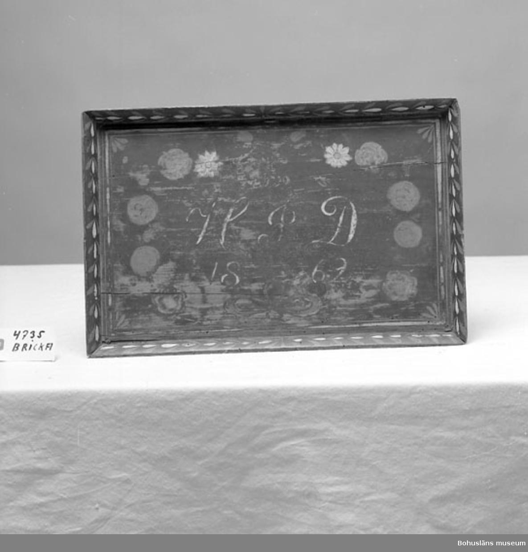 """435 Motivkat DEKORATIVT Rektangulär bricka med hög fasad kant. Svarvade små kulfötter i varje hörn. Svart färg i botten med dekor i rött, gult och vitt. Spegeln har en blomsterkrans med rosor och tulpaner samt röd rosett nertill. I mitten texten """"H I D 1862"""" i vitt och rött. Längs spegelns kant tre ränder i rött och gult. Den fasade kanten har en bladslinga i rött och vitt. Botten är tappad och skruvad. Spegelns färg är något bortnött. En mässingsring finns på en av långsidornas mitt att hänga den i. Inventerat 1996-04-29 AN Neg.nr UMFF 448, Kerstin Lychous dia 532  Ur handskrivna katalogen 1957-1958: Bricka av trä """"H.I.D. 1862"""" L. 46; Br. 30; H. 4 cm; 4 svarvade fötter; målad dekor i rött, gult och vitt. Sprickor och maskhål.  Lappkatalog: 66"""