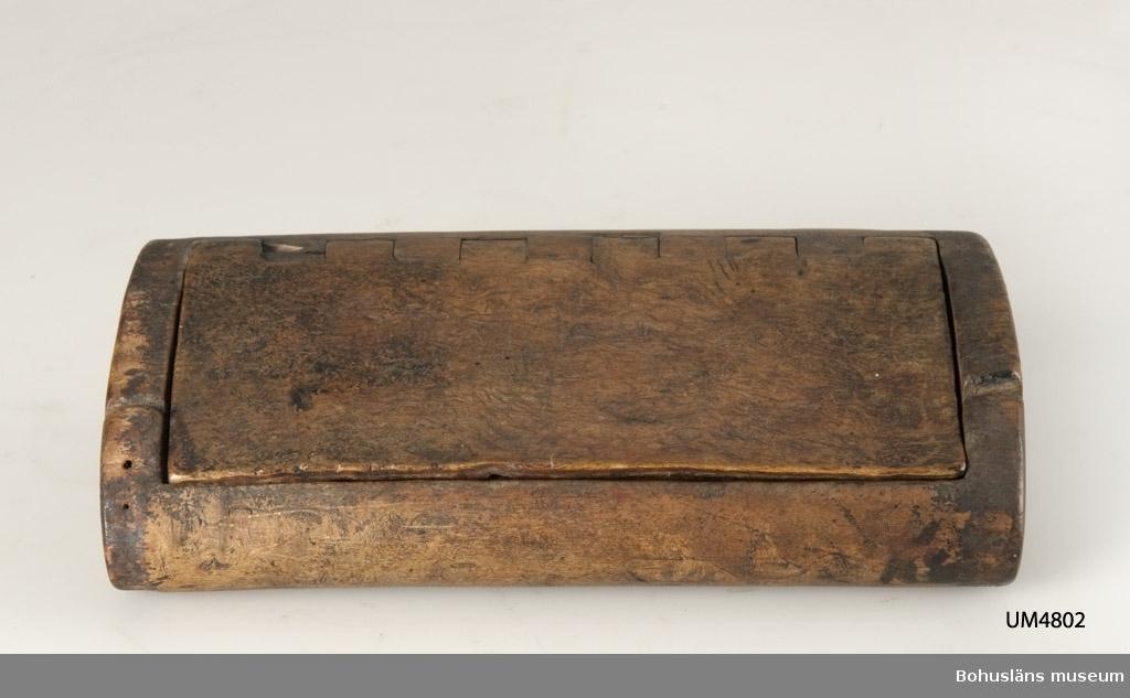Rektangulär ask med oval genomskärning, masurbjörk. Ovansidan har lock, vilket sitter fast genom dekorativ konstruktion. Betsad. Kortsidorna är spruckna. Inuti har flintbitar förvarats.  Ur handskrivna katalogen 1957-1958: Ask av björk m. flintbitar Askens L: 17,5 Br. 9,5 H: 4. Föremålet helt. - 9 spån, skrapor m.m. av grå flinta.  Lappkatalog : 1