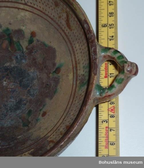 Ur handskrivna katalogen 1957-1958: Keramikfat m. öron Mynningsdiamet.: 15,8 cm. H.: c:a 6 cm. Lergods m. målning bl. a. i gult o grönt. Färgen delvis avflagad.   Lappkatalog: 63