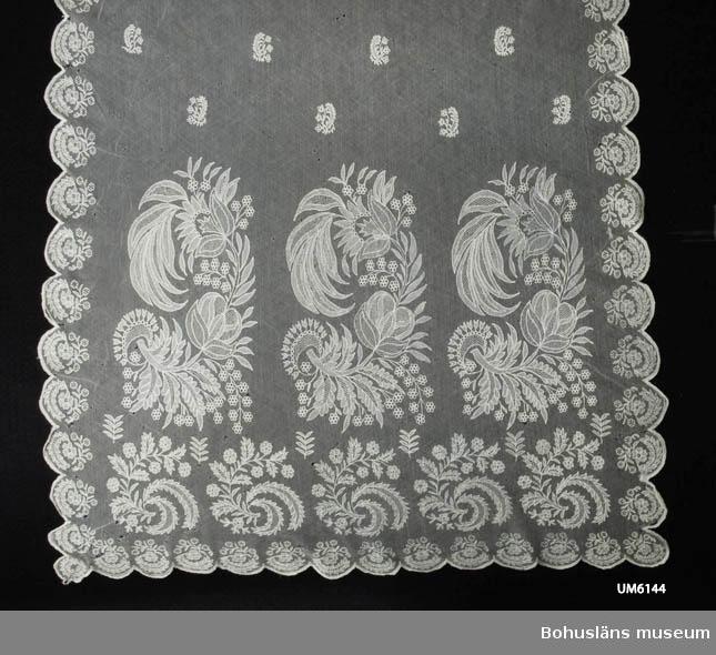 Föremålet visas i basutställningen Uddevalla genom tiderna, Bohusläns museum, Uddevalla. Vit schal av maskintillverkad bomullstyll med mönster av ca 40 cm breda broderade blomsterbårder vid kortsidorna och mindre blomstermotiv utspridda över hela ytan samt längs kanterna. Uddkant runtom. Blommotiven är stiliserade men ser på grund av mönstrets detaljrikedom tämligen naturalistiska ut. Broderiet har konturer i tambursöm och trädda partier i bottnarna på blommor och blad. Tyllens trådar dras på vissa ställen ihop av stygnen i bottnarna. Broderiet gjort för hand. Vid schalens uddkant är dock fatssydd en picot-kant (band med små öglor i ytterkanten) som är maskintillverkad.  Ur handskrivna katalogen 1957-1958: Axelschal från början av 1800-talet. L. c:a 2,95 x 0,60 m. Av vit spets med blommönster. Smärre hål. - Tillhört fru Laura Brunius född i slutet av 1700-talet.  Har enligt äldsta katalogen tillhört Fru Laura Brunius född i slutet av 1700-talet. Släkten Brunius kom till Varberg från Danmark 1725. I Tanum fanns prosten Gomer Brunius bosatt kring år 1800. Uppgifter om vem Laura Brunius var har ej gått att få fram med hjälp av tillgänglig litteratur.  En maskin för tylltillverkning uppfanns 1808 i England. Därav den ungefärliga dateringen till tidigast 1810. Två lagningar nära ena kortsidan, en lagning mitt på. Många hål, små och mycket små. På ett ställe bruna fläckar.