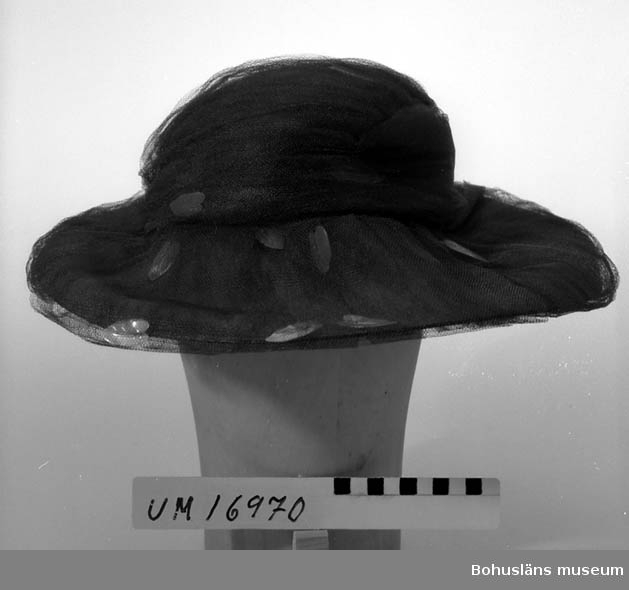 Slätt kulle med brett brätte av svart, fin strå, klädd med svart tyll med fastsydda pärlemorlöv. Tillverkad för och använd vid en mannekänguppvisning vari Strand Mode deltog 1960.  Se UM16935.