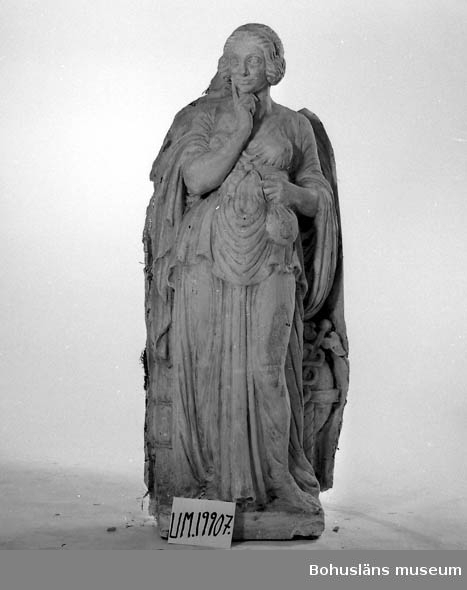 """Gipsförlag till skulptur föreställande kvinna """"gudinna""""? som står och tänker. Klädd i antik, lång tunn och veckrik dräkt samt hållandes en penningpåse? i handen.  Hon står på en 9 cm hög sockel, något skadad. Förlagan är uppbyggd på en stomme av trä och fylld ett stråmaterial samt juteväv.  Förlaga till skulptur/allegorisk figur i granit placerade i runda nischer på byggnaden Göta källare, Hotellplatsen, Göteborg. Utförda 1922. Fyra olika skulpturer finns varav Bohusläns museum har två av förlagorna.  Lös del avslöjar att även denna förlaga varit signerad J.A. Wetterlund, jfr UM19906. Konstnären har gjort förlagan till lejonen i brons framför universitetsbyggnaden vid Vasaplatsen, Göteborg.  Litteratur: Se Svenskt konstnärslexikon del V för att få ytterligare upplysningar om hans verk. I Västgötagenealogen 1992:4 finns artikeln """"Johan Axel Wetterlund - slottsskulptören från Västergötland"""", Stieg-Erland Dagman, Habo."""