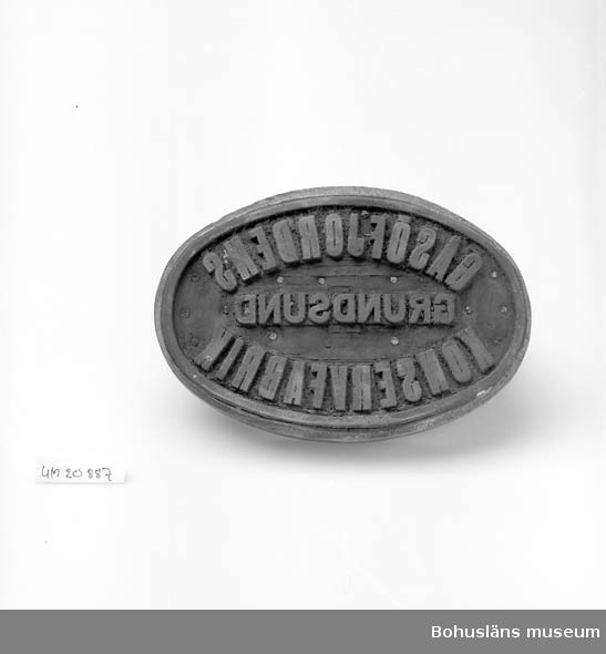 """594 Landskap BOHUSLÄN  Oval trästamp med handtag, tryckplatta i gummi med texten: """"Gåsöfjordens Konservfabrik, Grundsund"""". Använd till silltunnor och dyl."""