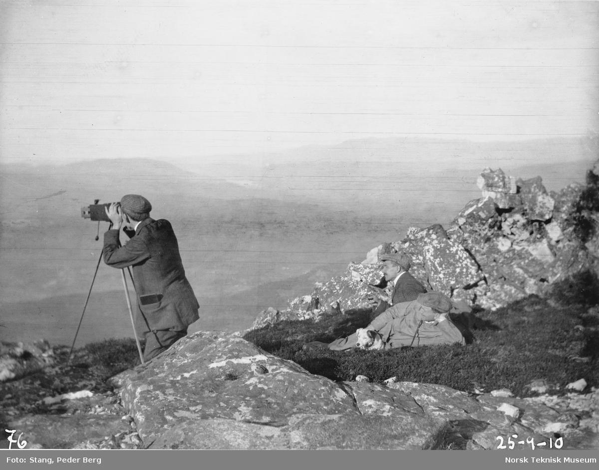 Tre menn og en hund på fottur på Lifjell, Sandvold fotograferer