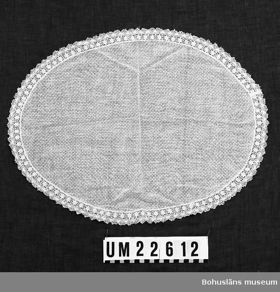 594 Landskap BOHUSLÄN  Oval vit duk med invävda ljusgula prickar. Runt kanten påsydd spets.  UMFF 123:3