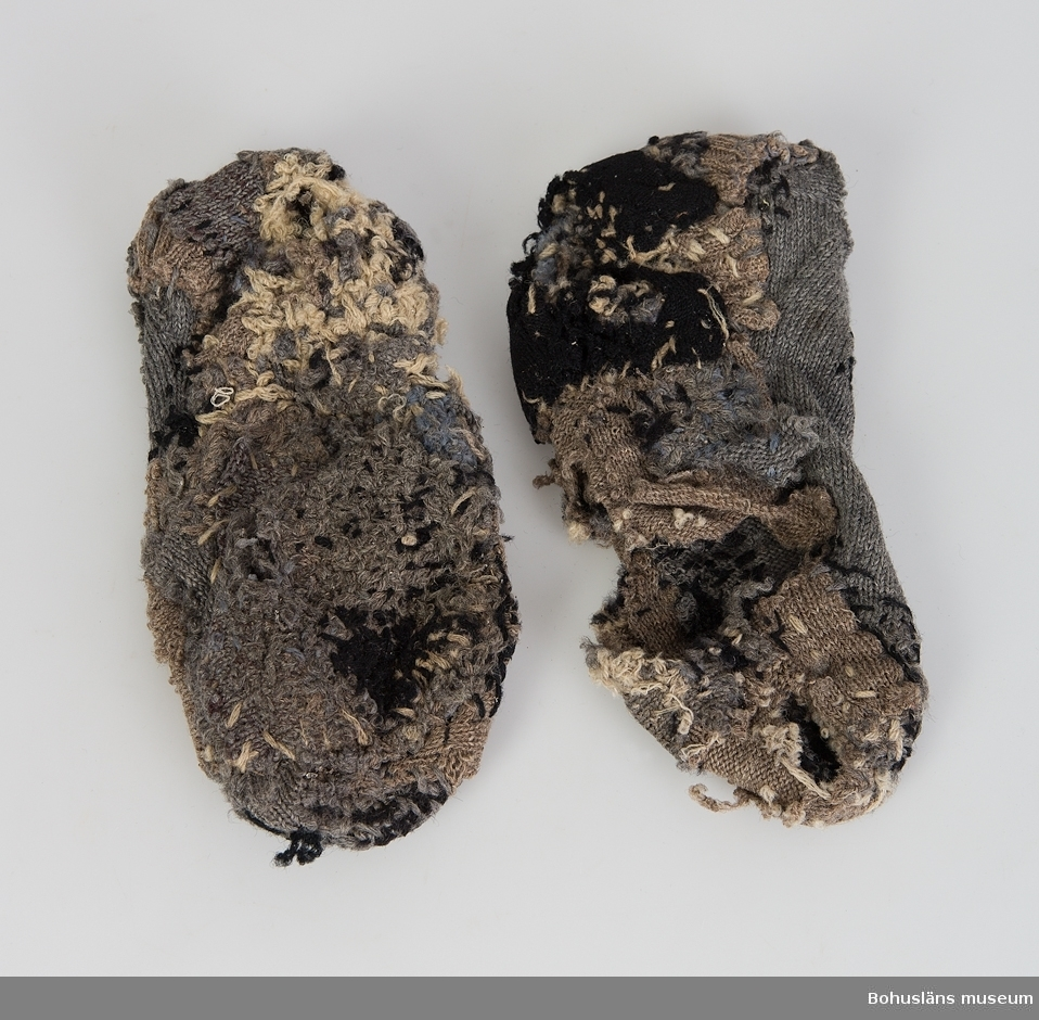 Skaftlös, ursprungligen grå socka som lappats med avklippta bitar av bruna och svarta sockor. Mycket stoppade. En socka har stort hål under.