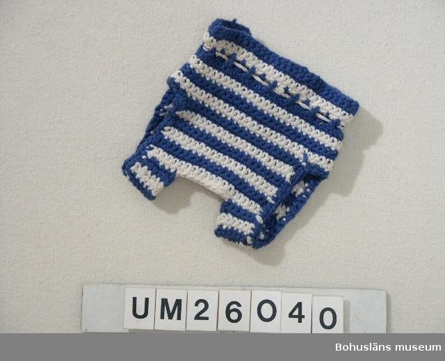 """Blåvitrandig. I midjehöjd tvinnat vitt bomullssnodd som löper i dragsko och avsett som """"skärp"""". Person- och släktuppgifter se UM026024"""
