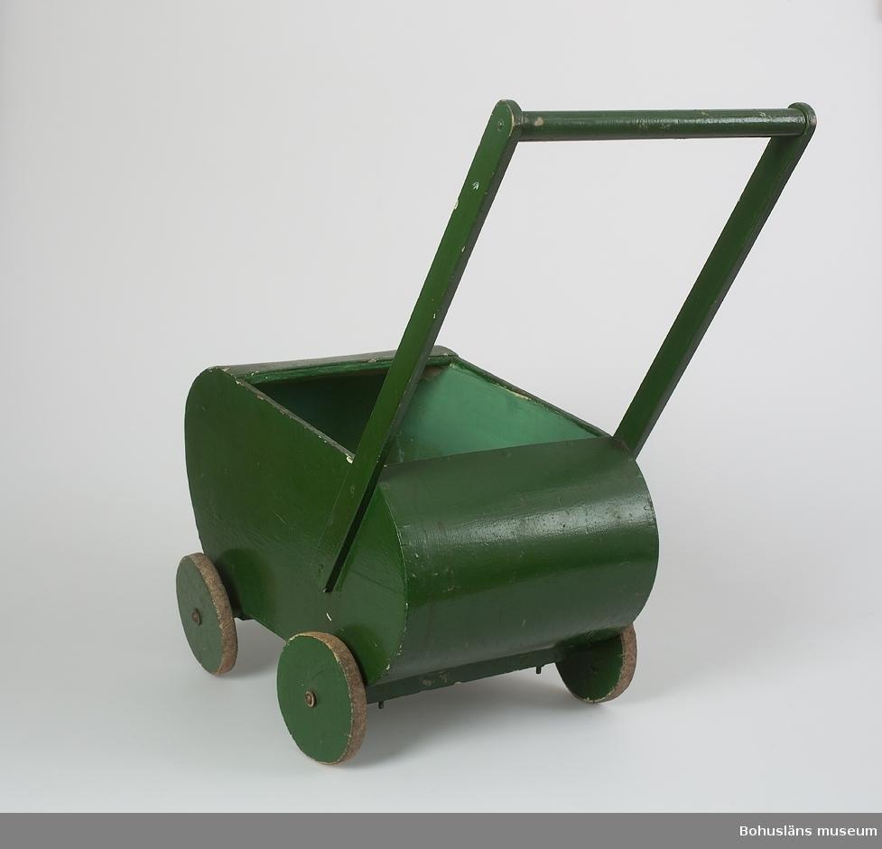 Grönmålad dockvagn. Rundade gavlar. Trähandtag. Ett av hjulen sprucket, lagat genom zinkning. Systern Ulla hade en likadan dockvagn men blåmålad, se UM026084, även denna tillverkad av morbrodern Anders Jacobsson. Hjulen gick ibland sönder och fick ersättas. Därför åtta lösa omålade reservhjul av trä. Madrass saknas men har tidigare funnits.