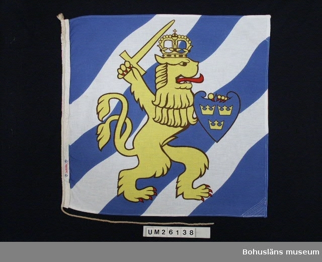 """Identifikationsflagga för ångaren """"Göteborg"""" tillhörande Ångfartygs AB Bohuslänska Kusten, som hade fartyg i linjetrafik med frakt- och  personbefodran utmed bohuskusten. """"Göteborg"""" gick mellan Göteborg och Oslo och Gösta Svedung var dess befälhavare under större delen av sitt yrkesverksamma liv. Flaggan har ett på vardera sidan tryckt motiv av Göteborgs stadsvapen, ett gult lejon med kungakrona, röd tunga och röda klor. I vänstra tass  höjt, gult svärd och i högra blå sköld med tre gula kronor (lilla  riksvapnet) allt med bakgrund av tre vita och två blå linjer. Symbol för ångaren """"Göteborg"""" Jämför signalflaggor med samma användning UM026139 - UM026168 Fabriksetikett:""""Stormduk"""" mellan två logotype """"HG"""" i övre linje på  en nedåtspetsig triangel.  Personuppgifter se UM026024"""