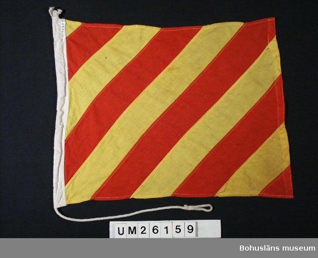 """Diagonalt ställda, omväxlande röda och gula band.  Betyder: """"Jag draggar"""".  Användning se UM026139  Personuppgifter se UM026024"""
