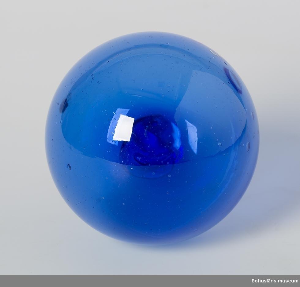 """Av blått glas. Rester av etikett med text: """"--de i- ---w--""""."""