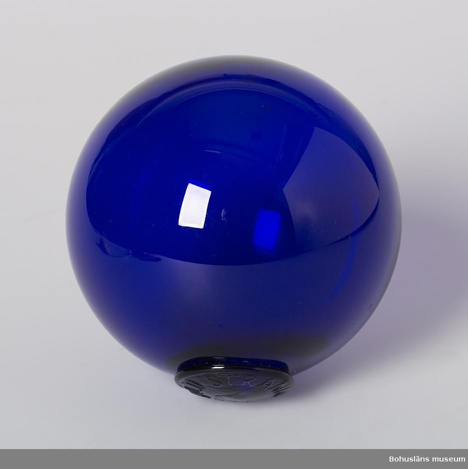 """Mörkblått glas. På glasplomb instansat i svag relief: """"Torvald Stranne""""."""