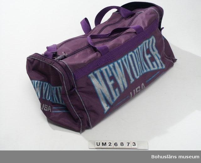 """Väska, sk. sportbag, av lila (rödblått) syntetfibertyg belagt med plastmaterial på baksidan (polyamid och PVC?). Avlång form. Rektangulär bottenplatta. Nästan kvadratiska sidostycken. Ett stort fack i mitten som öppnas upptill med två blixtlås på längden. När väskan är öppnad bildas ett lock som sitter fastsytt vid sin ena kortända och som har blixtlåsdelar längs sidorna. Blixtlås av plast men ringar att dra dem med av metall (nyckelringar?). Två mindre fack, ett på varje sida, som öppnas med blixtlås på tvären. Längs sömmarna finns passpoaler av hårt syntetband i grått, grönaktigt blått (turkos) och rödblått (lila). Tryck på sidorna i samma färger: stora bokstäver: """"NEWYORKER USA"""". Bärhandtag av kraftigt rödblått (lila) syntetband fastsydda på långsidorna. Bärrem för att bära väskan på axeln fastsydd på ovansidan. Den regleras med svart plastspänne. Lös bottenplatta invändigt av svart plast med pappskiva inuti?. Ena lilla fackets blixtlås trasig.  Köpt 1990, förmodligen på Mats Sport, Backaplan, Göteborg. Använd att packa kläder i. Har använts i alla år på båtsemester. Väskan har också använts t ex på resor till fjällen och när Anders har rest till USA.  Insamlad i samband med SAMDOK-dokumentation av båtturism.  För mer information om brukaren och dokumentationen se UM26869."""