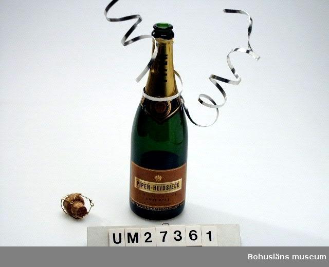 """Champagneflaska (:1) i grönt glas med pappersetikett om hals och buk, 750 ml. Serpentin av silverfärgad mjuk metall virad runt flaskhalsen. Kork (:2) med text """"Piper"""" och tillslutning av virad metalltråd. Flaskan är brukad i samband med nyårsaftonsupé för fyra personer.  Se även Bilagepärmen UM27361 för exempel på varningsartikel som publicerades i pressen i januari 2000 med anledning av exploderande cider- och champagneflaskor.  För information om Millennieinsamlingen, se UM27360."""