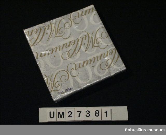 """Format avser förpackningen.  Cellofanförpackning med silverfärgade pappersservetter, format 20 x 20 cm. Servetterna dekorerade  med texten """"2000"""" i vitt samt däröver """"Millennium"""" i guldtryck.  Inköpt i Uddevalla för 49 kronor.  För information om Millennieinsamlingen, se UM27360."""