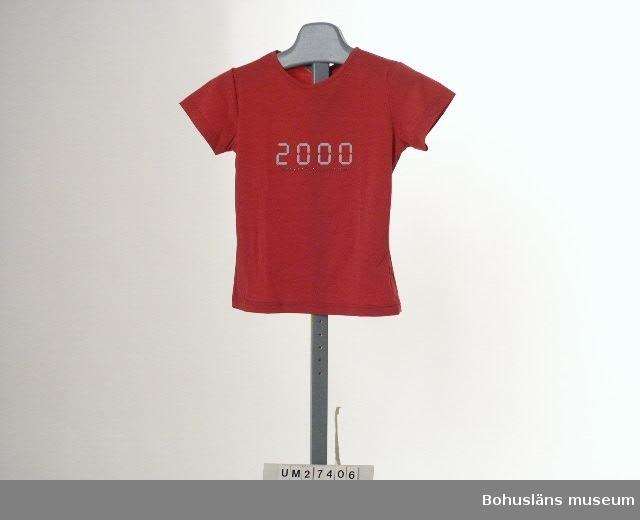 """Rosa t-shirt i töjbart konstmaterial med påtryck """"2000"""" i grått samt """"MESSAGE MILLENNIUM"""" i silverglitter,  inköpt i Uddevalla för 299 kronor. Storlek small. Plagget märkt med två vidhängande pappersetiketter med skötselanvisning.  För information om Millennieinsamlingen, se UM2736"""