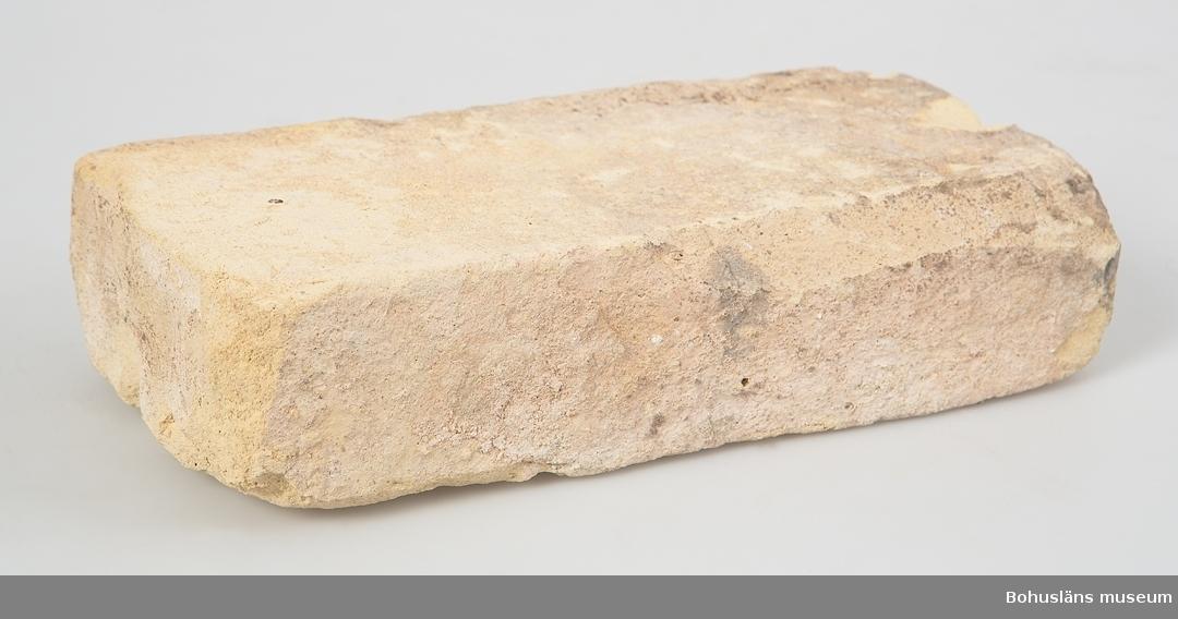 Tegelsten av gult lergods. Murbruksrester. Teglet har ingått i den byggnad som utgjorde Kampenhofs bomullsspinneri i Uddevalla,  byggd 1858 och riven 1982.  Byggnaden fick på sin tid pris som Sveriges vackraste industribyggnad.  Dessa tegelstenar återanvändes i Bohusläns museums första basutställning, delen Stadsbor där de utgjorde del av en uppmurad vägg med tegel från fabriken på den s. k. bakgården i avsnittet om industriarbeterskorna på Kampenhof. Materialet togs in till samlingarna i samband med att utställningen revs november 2005.  Litt: Eriksson, Ulf G. och Klasson Gunnar: Historien om Uddevalla, 1995. Åberg, Martin: Uddevalla stads historia 1860-1998 / Martin Åberg på uppdrag av Uddevalla kommun .1997