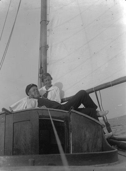"""Enl. text i blå bok: """"Man och dam på rufftaket, segelbåt."""" ::"""