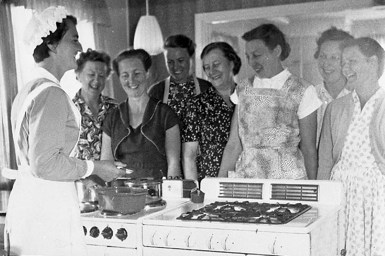 """Kursen """"Rationell matlagning"""" på Martapråmen Åstol år 1958. Barbro Östlund  (längst till vänster) tillsammans med kvinnor kring två spisar"""