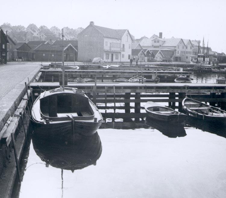 """Noterat på kortet: """"Gravarne Hamnbild ca. 1950. Byggnaden mitt på bilden kungshamns- fiskarnas nybyggda fastighet. Till h. AB Bröderna Amelns lagerbyggnad""""."""