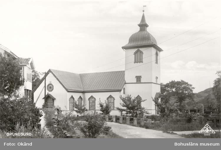 """Tryckt text på kortet: """"Grundsund."""" Noterat på kortet: """"Grundsund Skaftö(landet). 3 Juli 1955."""" """"Kyrkan fr. nv."""""""