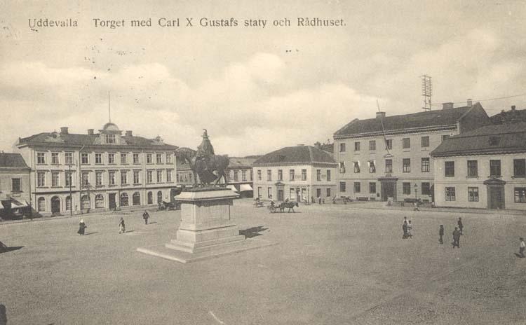 """Tryckt text på kortet: """"Uddevalla. Torget med Carl X Gustafs staty och Rådhuset."""" """"Uddevalla Pappershandel, Hildur Andersson."""""""