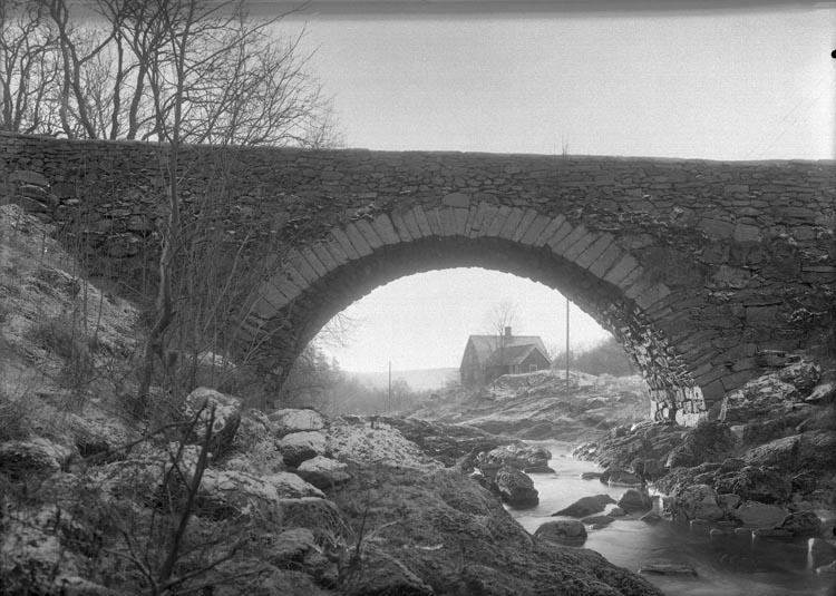 """Text som medföljde bilden: """"1937. 23. Stenbron och stugan tagit nere vid älven.""""   Uppgifter från Munkedals HBF: """"Gamla stenbron. Munkedalsälven. Snickarbostaden""""."""