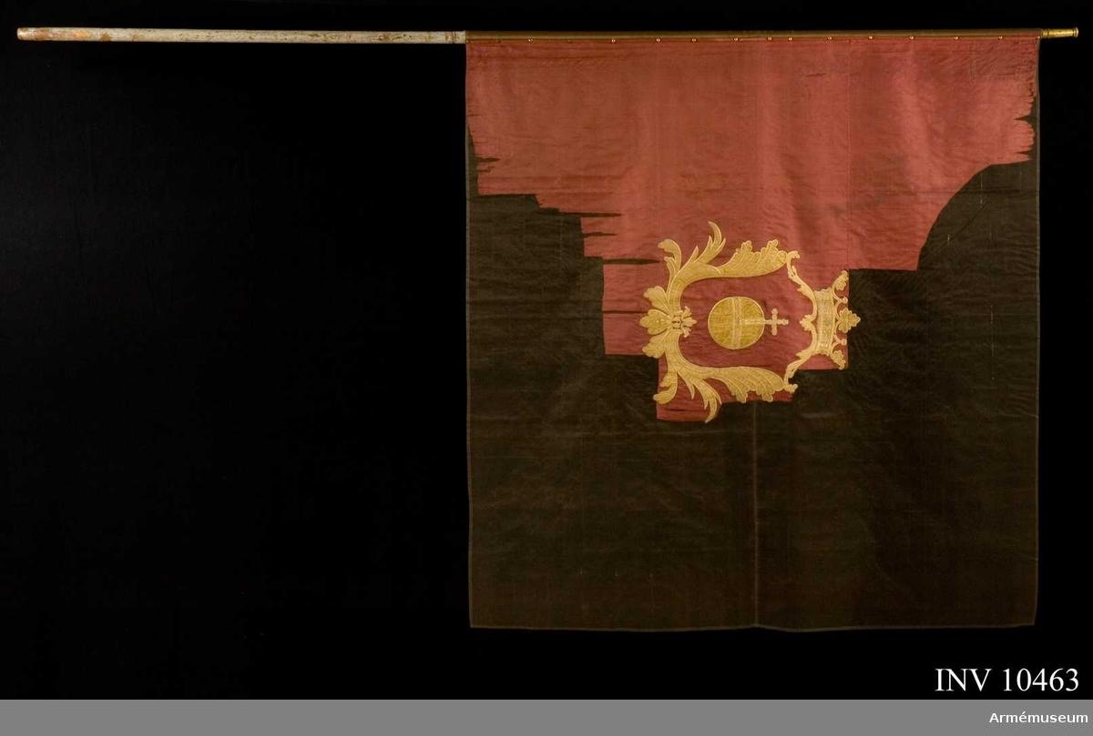Grupp B I.   Fana av röd sidenkypert varå broderat lika å båda sidor Upplands   vapen, ett riksäpple i gult siden och silke å rött fält i en av   rococobladverk bildad krönt öppen krona, utförd i gult siden och silke.