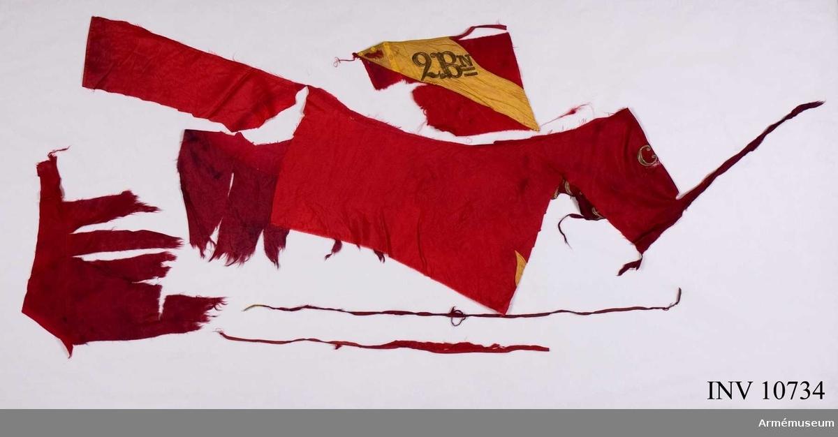 Grupp B.  Duk av rött fansiden i tre våder med från hörnen inåtgående flammor, gul kontur i silke. Rött kantband. Vapen saknas. Segernamn Clissow 1702, Bataljonsnamn 2 B:n.