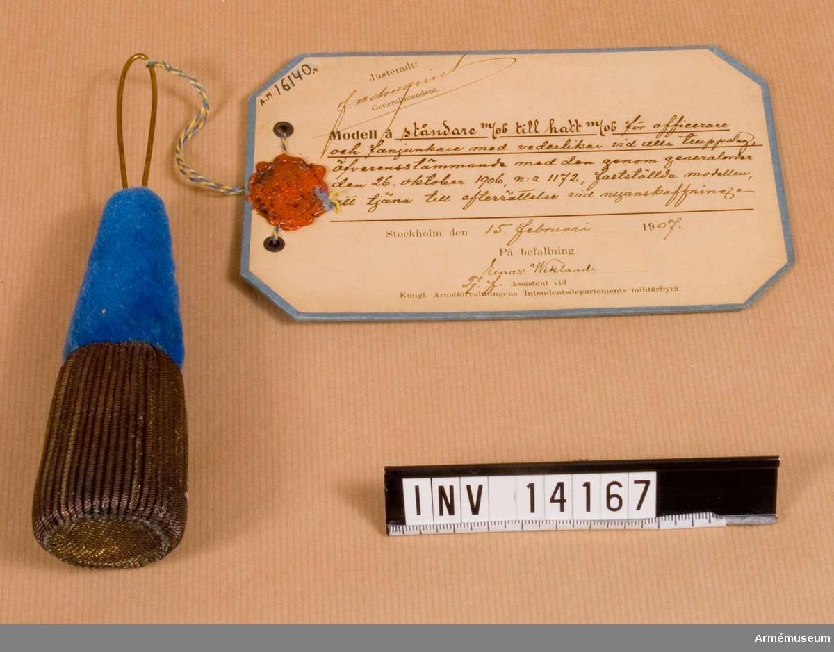 """Grupp C I. Vidhängande modellapp med text: """"Modell å ståndare m/06 till hatt m/06 för officerare och fanjunkare med vederlikar vid alla truppslag, öfverensstämmande med den genom generalorder den 26 oktober 1906, nr 1172, fastställda modellen, att tjäna till efterrättelse vid nyanskaff. Stockholm den 15 februari 1907. På befallning, Einar Wikland, Tj. f. Assistent vid Kongl. Arméförvaltningens Intendentsdepartements militärbyrå."""""""