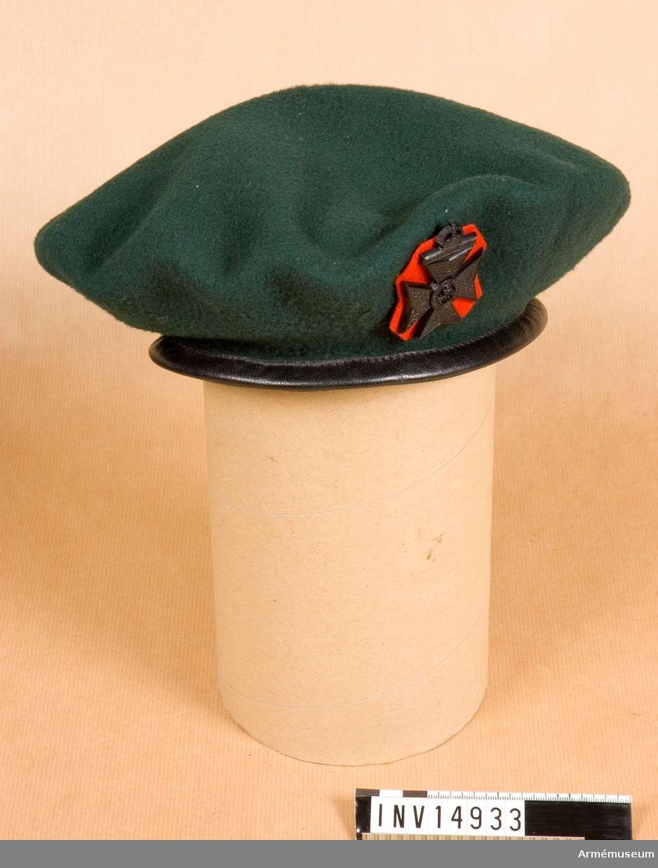 """Grupp C I. Rund. Staffordshire. Med regementsnamn av grönt kläde m svart lädearkant. Inuti ett svart silkeband varmed baskern görs större eller mindre. Fodret av svart bomullstyg m påskrift """"7"""", """"Kangol  Wear Limited"""" (= Kangol Klädes AB), """"1944"""". På ena sidan finns två lufthål och på andra sidan regementsvapen m rött kläde under. Vapnet är ett kors m krona ovanpå. Över korset påskrift på latin """"Celer at audax"""". I mitten har korset reg.emblem och runt om står reg:s namn """"The Kings Royal Rifle corps"""". På var särskild del av korset står m små bokstäver namnen på de platser där reg. utkämpat fältslag och datum f dessa. PUBL  AMV Meddelande IX, sida 38.Enl kapten W Granberg."""