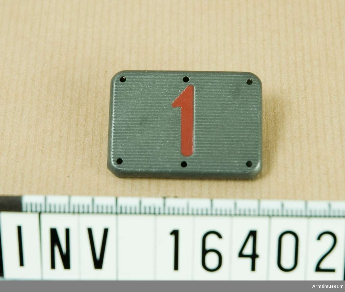 Samhörande gåva är: 16399-16409.Förbandsbeteckning m/1934.Truppförbandsbricka av metall. Grå botten med siffran 1 i rött. Brickan försedd med sex nabbar för fastsättning. Truppförbandsbrickorna utgick ur utrustningen gemon go nr 4345  1950-12-02.