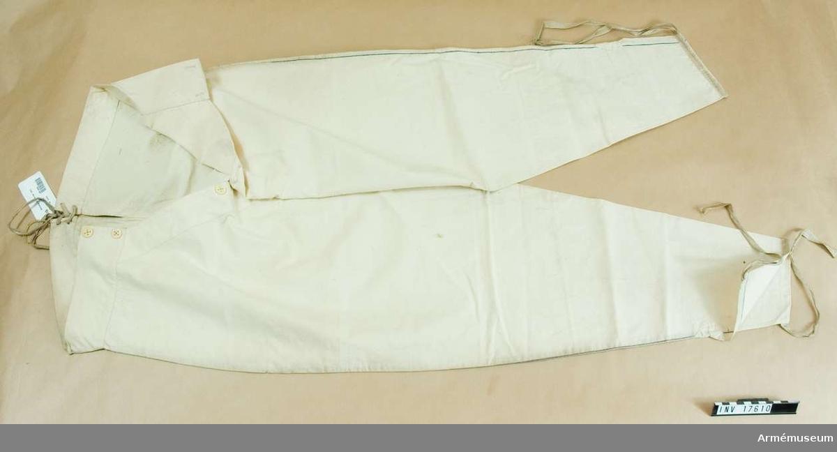 """Grupp C I. Kalsonger, Frankrike. 1864. Det första paret kalsonger är av vitt bomullstyg med blå rand vid yttersömmen. På framsidan sprund med tre vita benknappar. Baktill ett litet sprund och bomullsband. Nederst på båda benen sprund med bomullsband. På baksidan stämpel med påskriften: """"Chauveaux & Blanc fils Paris"""". Kalsongen har en pappersetikett med text """"Equipements  Militaires. Chauveau & Blanc Ainé, Rue des Petits Hotels 26 Pres  la place Laffayette, Paris"""". På andra sidan ett rött sigill.  Modele Ministériel. 3 tailles (över varandra siffrorna) """"1 2 3""""   (samt) """"1/4 - 1""""Fr. 1,70"""" """"2/4 - 2"""" Fr. 2,35"""" """"1/4 - 3"""""""" """"Pris  avant la guerre d'Amérique et aujourd'hui Mai 1864"""" -  Ministeriets model, 2 tillskärningar -1/3 - 1 och 2/3 - 2.  (Textdelarnas inbördes ordning osäker på förlagan - BoM).  LITT  Collection complete des tracés de coupe des Effets d'Habittement a l'usage de tous les corps de l'armée, 1845-47 pour la Commission des modeles. Sid 3 Ritning av kalsonger med mått. Enl kapten W. Granberg."""
