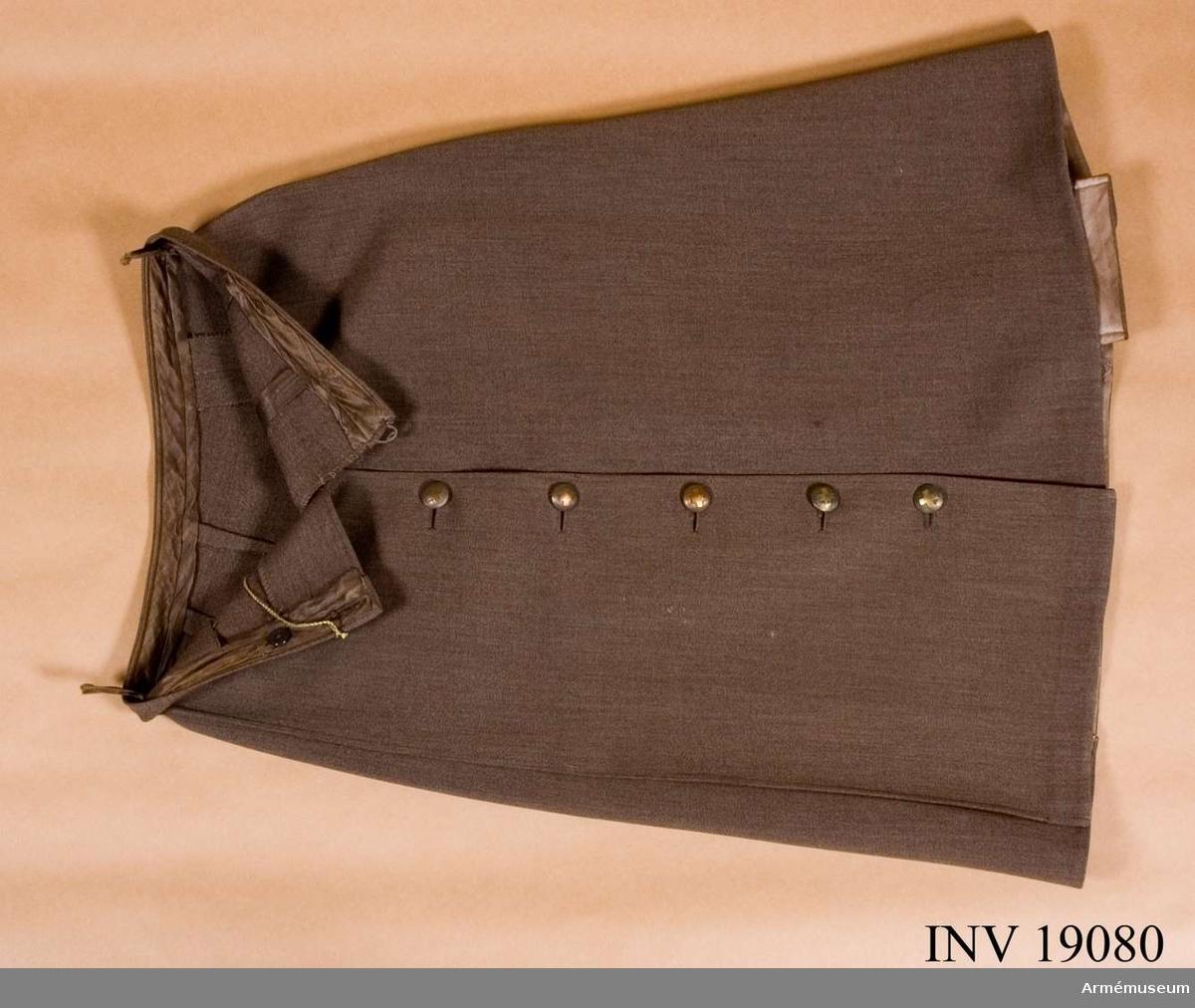 Samhörande nr är:19079-82, jacka, kjol, blus, axelklaffar. Kjolen går omlott och knäpps åt V sida med sju knappar av Röda korsets modell större, som Sporrong har tillverkat. Ett veck åt höger sida och ett motveck mitt bak. Linningen i midjan är ofodrad.