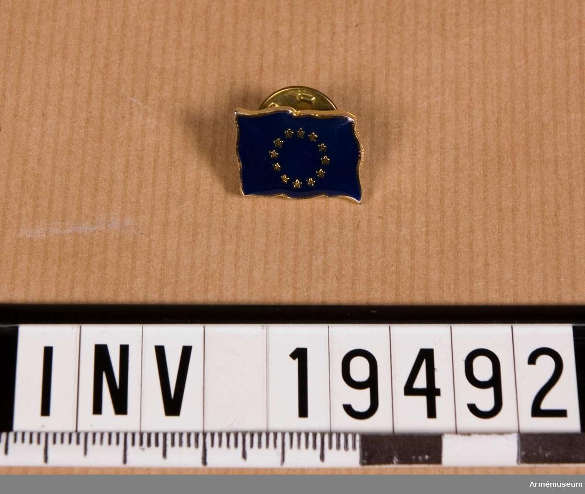 Flaggmärket i metall med blå botten och 12 gula stjärnor i ring. Fästanordning på baksidan.  Samhörande nr AM.19483-19494