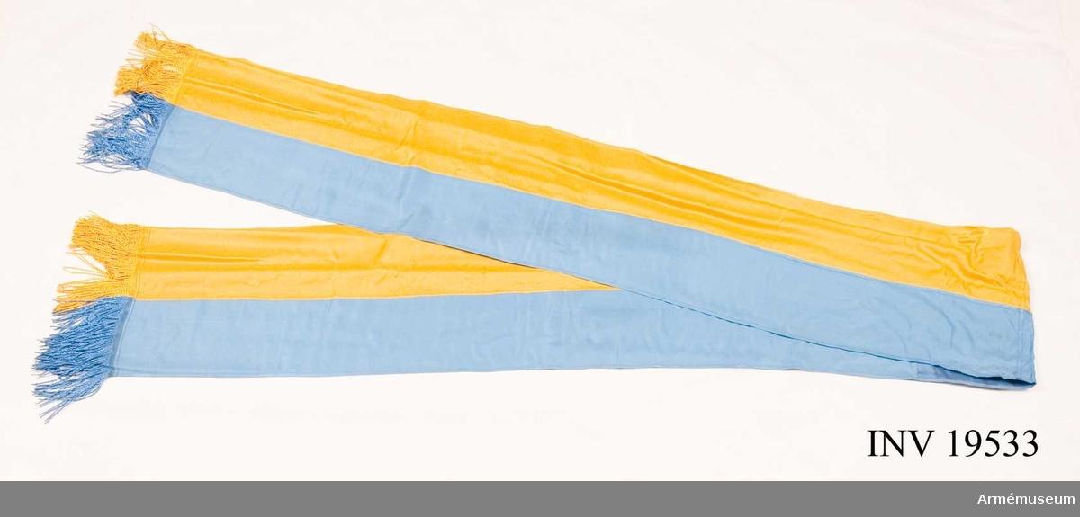 Kravatt till fana för Södermanlands flygflottilj. Kravatt med frans i silke.  Samhörande nr är AM 19531-19534, fana, spets, kravatt, fodral.
